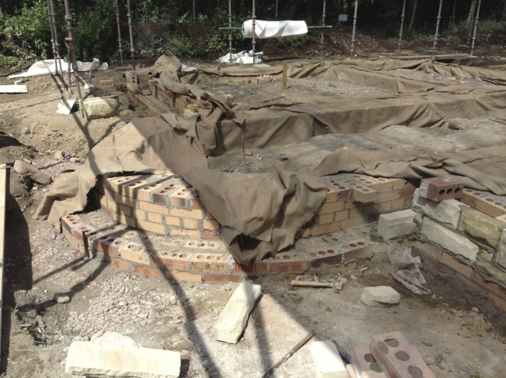 The curved front of the boot room in brick, waiting for stone facing