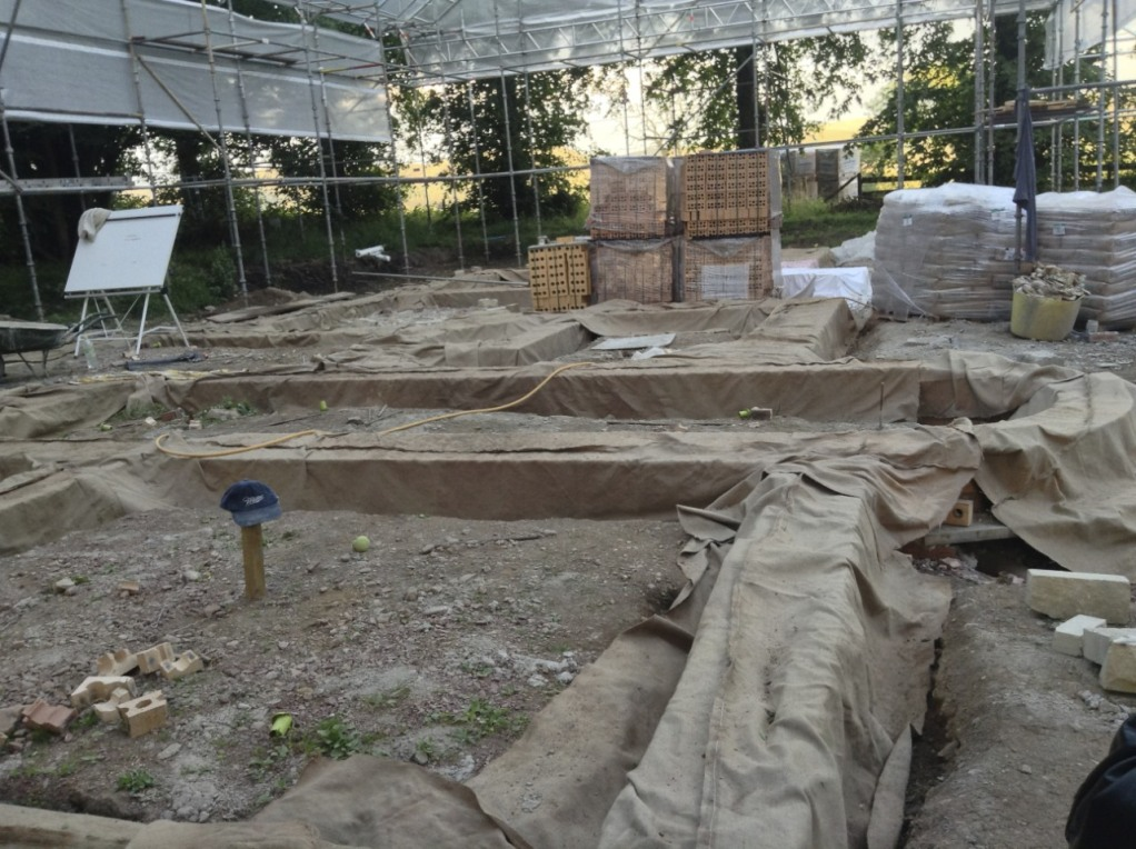Looking across the main house with the first layer of bricks delineating the walls