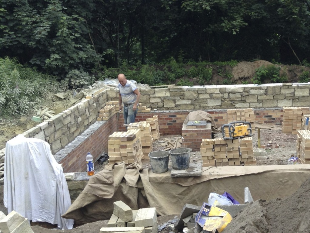 Bricks and stone being laid on top of the DPC for the Peerie Hoose plinth walls