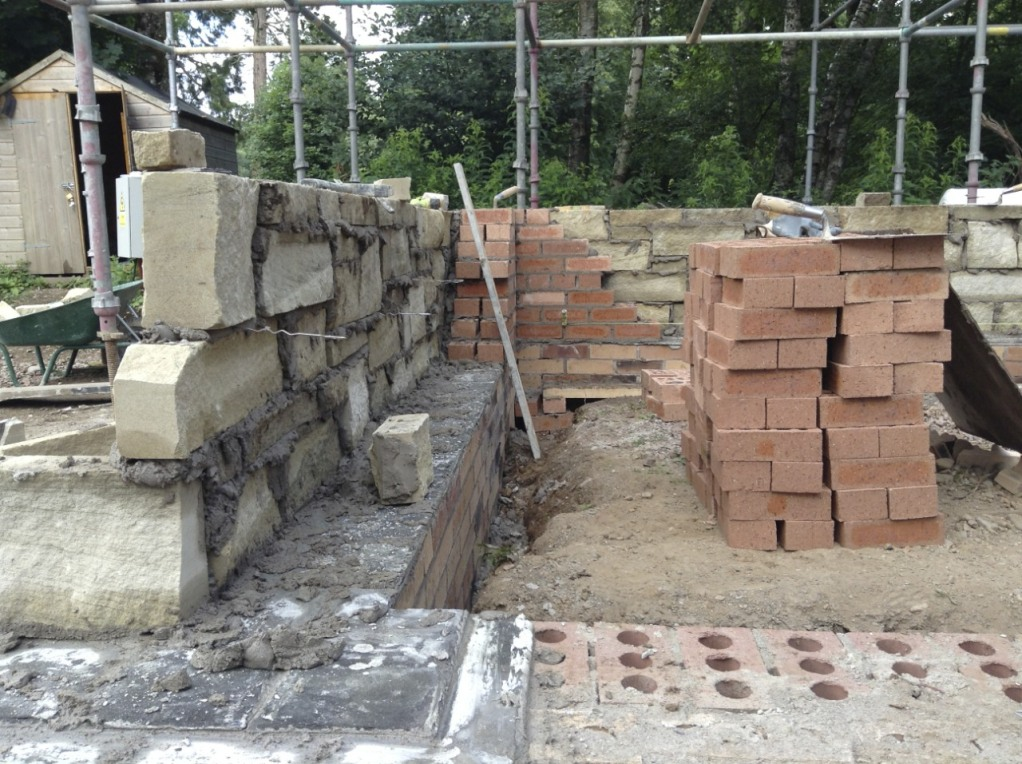 Building bricks behind stone facing, showing metal strips that tie the stone and brick walls together